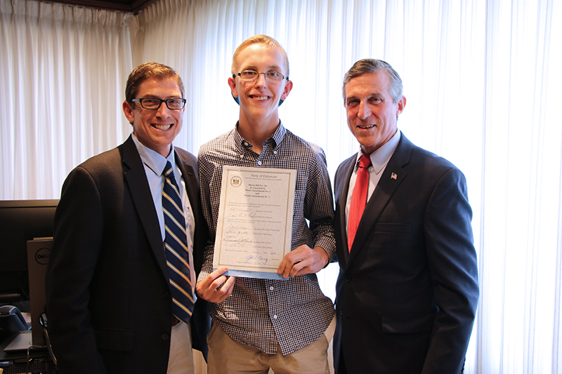 CDS Associate Director Brian Freedman, Cape Henlopen High School student Zach Simpler, and Gov. John Carney pose at bill signing
