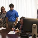 Governor John Carney signs HB 326 into law as advocates look on