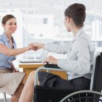 Female colleagues exchange a greeting, one is in a wheelchair