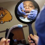 Child with disabilities gets teeth examined by dentist