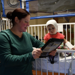 doctor looking at medical chart and child patient