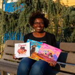 A Black woman sits on a bench with picture books spread out on her lap. Each book cover has a nonwhite character pictured.