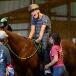 Young man rides horse during therapeutic horseback riding session