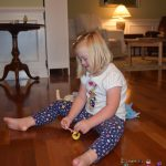 Natalie Rohe plays with toys on the floor