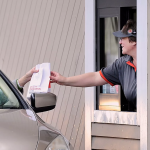 A Burger King employee serves a customer through the restaurant's drive-through window