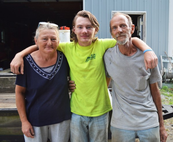Phillip Hartman, center, stands with his parents Faith and Mark near their Laurel home.