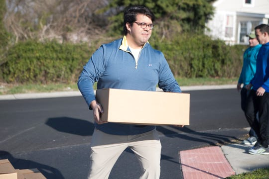 Senator Anthony Delcollo carries a box of food into the Absolam Jones Community Center.