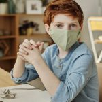 a boy wearing a face mask sits at his home desk