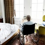 Elderly woman alone in wheelchair at long-term care facility