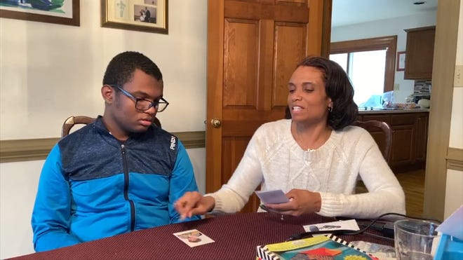 Malika Simmons and her son Eli, who has autism spectrum disorder and severe learning disabilities, work on a lesson together in their home.