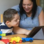 A child with a disability and his mother look at a tablet device together and smile