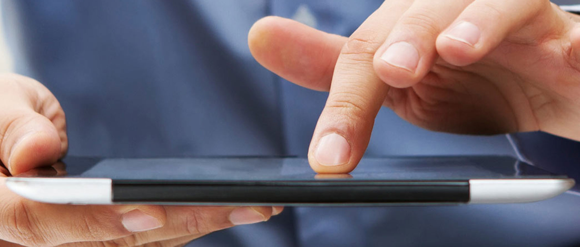 A person with a finger on a tablet device they are holding flat in their other hand