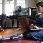 female college student with prosthetic leg sits on floor and works on a laptop