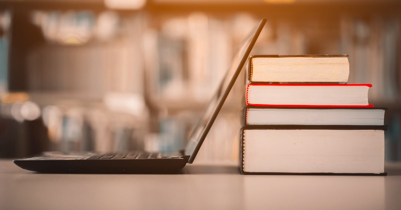 open laptop and reference books stacked in a library study environment