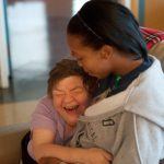 A resident and worker embrace at a intermediate care facility