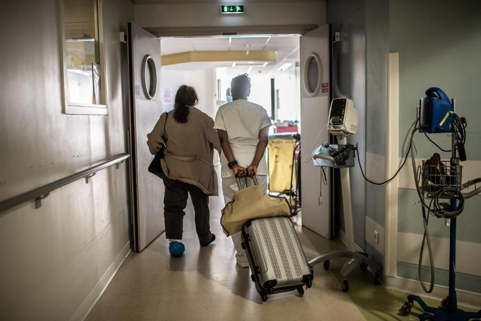 A nurse pulls a suitcase as she helps a patient
