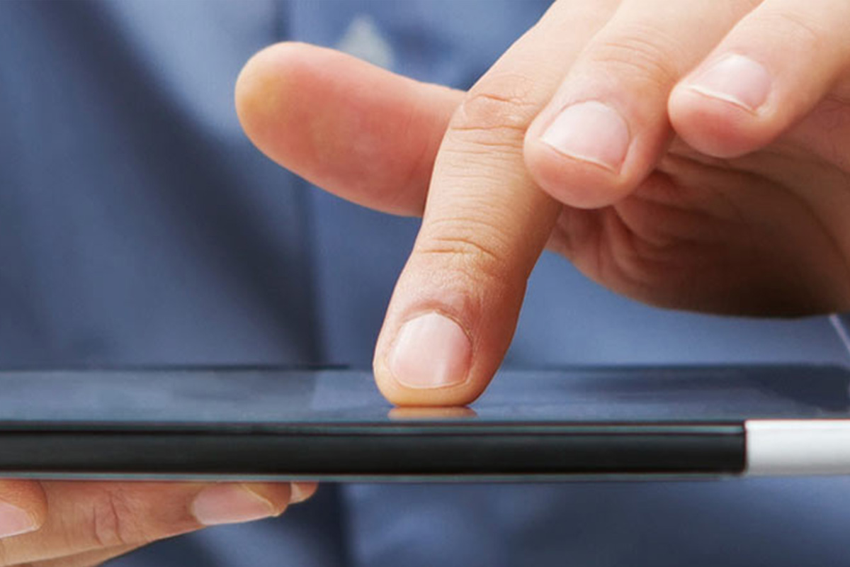 finger touching tablet device surface while cradled in other hand