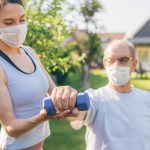 A home care aide wearing a mask assists an elderly man wearing a mask doing an arm exercise.