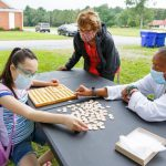 Two special education teachers works with a student on the lawn outside her house