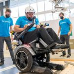 A man uses an experimental powered wheelchair while a team of engineers and researchers watch.
