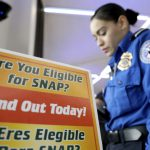 A brightly colored sign reads Are you eligible for SNAP? Find out today. In the background a woman in a TSA uniform stands with her head down