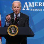 President Joe Biden speaks at a podium while behind him words read American Rescue Plan